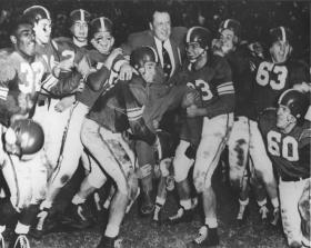 Players lift Coach Munn at the Rose Bowl, 1954 title=Players lift Coach Munn at the Rose Bowl, 1954